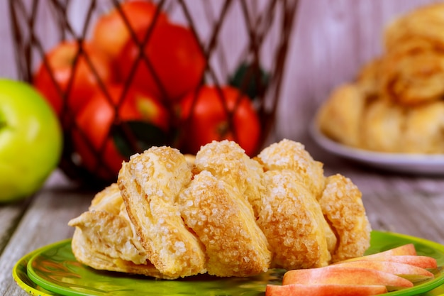 Apple strudel with fresh red and green apples in basket on table