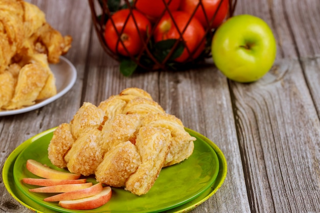 Apple strudel with fresh red and green apples on table