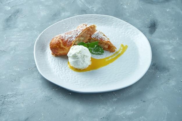 Яблочный штрудель с мороженым и красным джемом в белой тарелке. австрийская выпечка