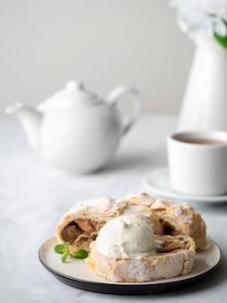 Apple strudel with ice cream and cinnamon. baked cake and tea, delicious dessert on the table.