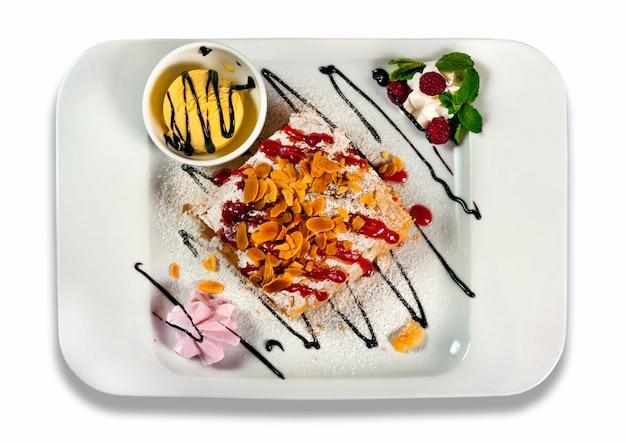 Яблочный штрудель с мороженым на белой тарелке, изолированные на белом фоне