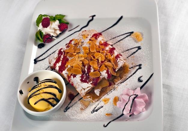 Яблочный штрудель с мороженым на белой тарелке
