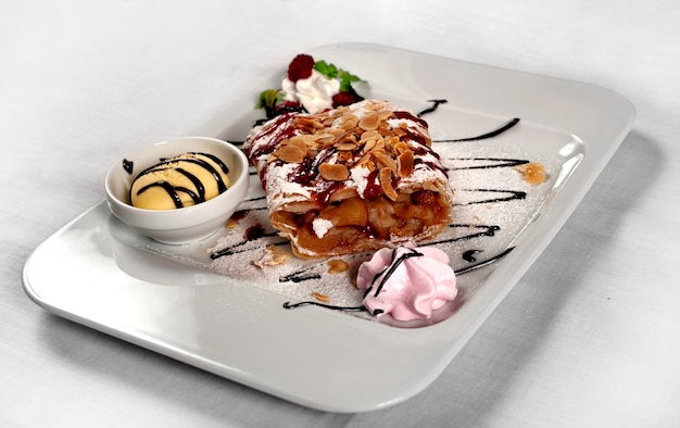 Apple strudel with ice cream on white plate, isolated on white surface