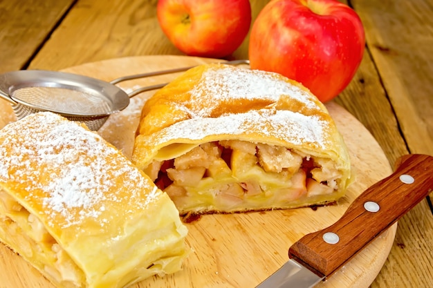 Apple strudel with icing sugar, apples, tea strainer, knife on a wooden boards background