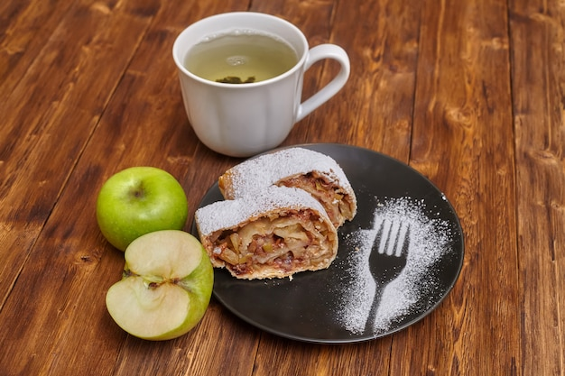 Apple strudel with icing sugar on black plate, wood