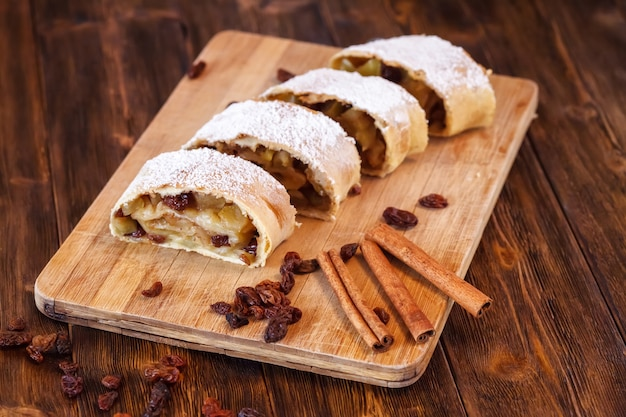 Apple strudel with icing sugar, cinnamon sticks, wooden surface