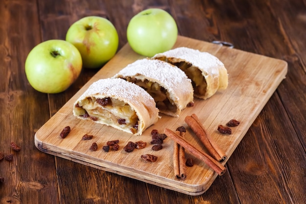 Apple strudel with icing sugar, cinnamon sticks, wooden table