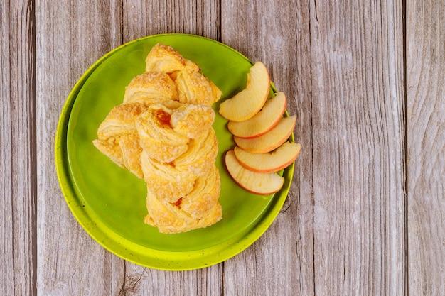 木製のテーブルにスライスした新鮮な赤いリンゴとリンゴのシュトルーデル