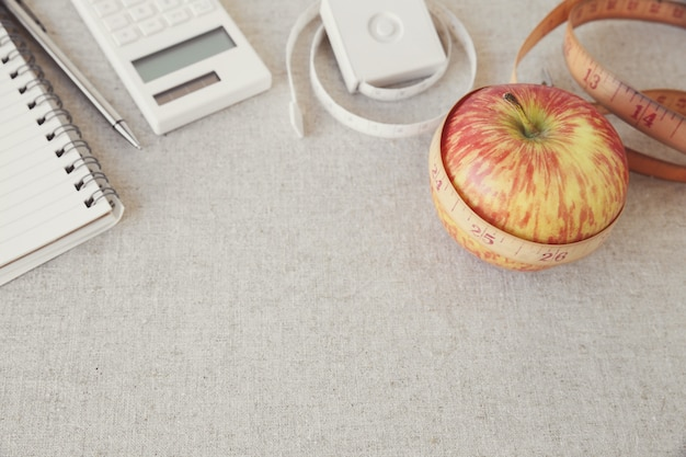 Apple, tape measure, notebook and calculator background for diet plan, weightloss plan