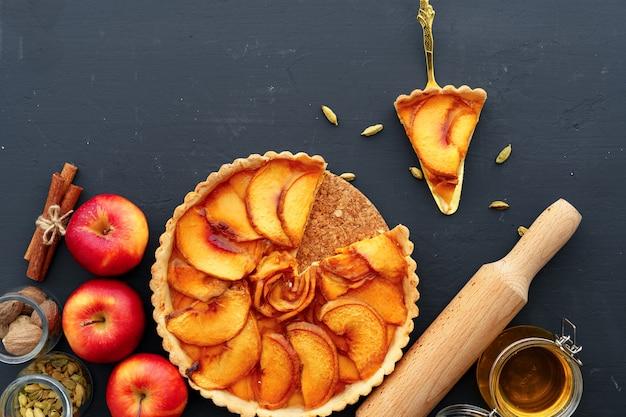 リンゴのタルトパイと木製のテーブルの上の赤いリンゴがクローズアップ