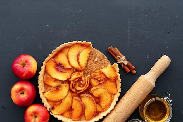木製のテーブルにリンゴのタルトパイと赤いリンゴ