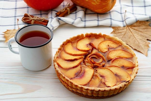 カボチャと乾燥した葉で飾られたテーブルの上のリンゴのタルトパイ
