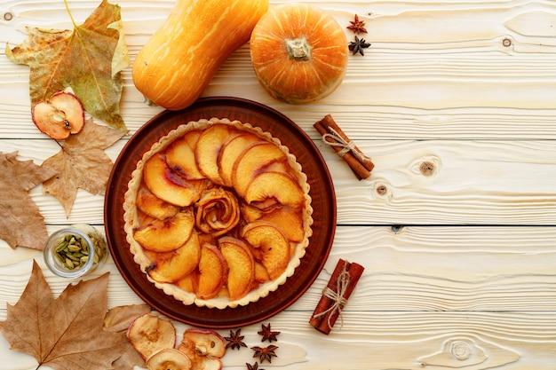 Яблочный пирог на столе, украшенный тыквой и сухими листьями