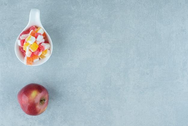 Una mela e una minuscola ciotola di caramelle su marmo.