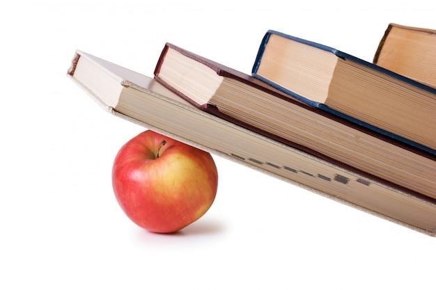 白で隔離される本の山の下でアップル