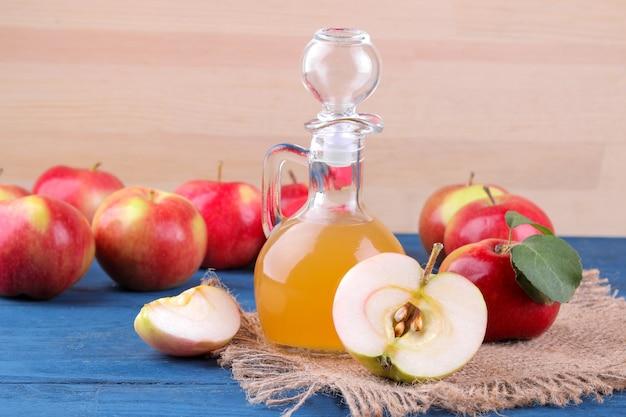 自然な木製の背景の青いテーブルの上の新鮮な赤いリンゴの横にあるリンゴ酢