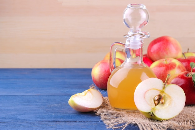 Apple  vinegar with  apples on a wooden background