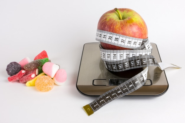 Apple over weight scale, measuring tape and jelly beans on white background