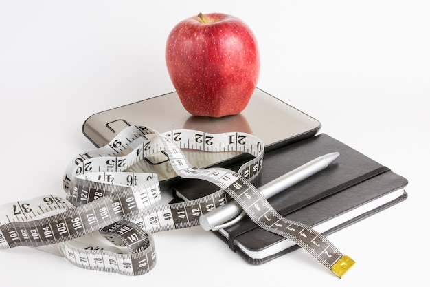 Apple over weight scale, measuring tape and notebook with white background