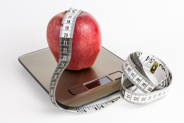 Apple on weight scale and measuring tape with white background