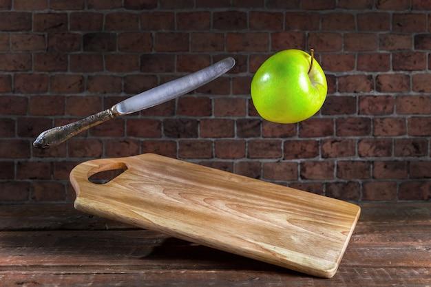 Яблоко с ножом и разделочной доской на фоне кирпичной стены. левитация.
