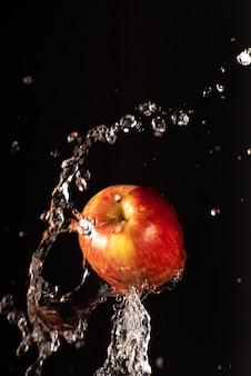 黒の背景と選択的な焦点と水の美しいスプラッシュとリンゴ。