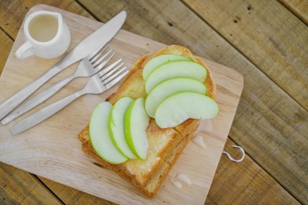빵과 사과 나무 접시에 제공