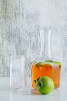 Apple with drink, ice cubes in glass on white and grungy, side view.