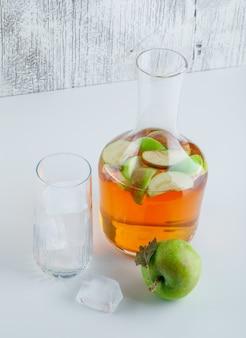 Яблоко с напитком, кубики льда в стекле на белом и шероховатом, под высоким углом.