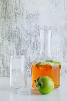Яблоко с напитком, кубики льда в стекле на белом и шероховатом, вид сбоку.