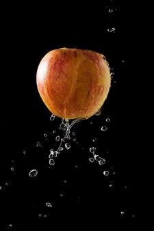 暗い背景に水滴が落ちるアップル