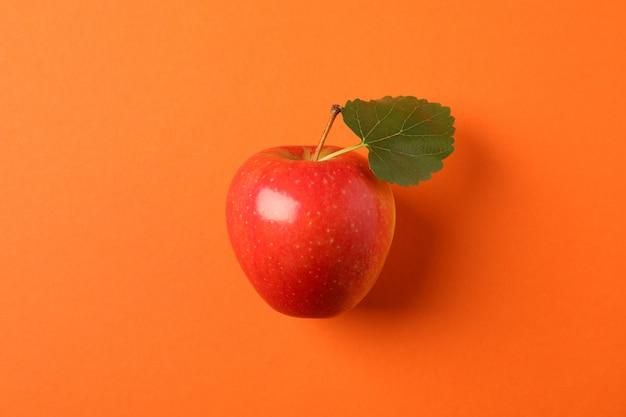 オレンジ色のテーブルの葉とリンゴ