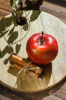 Яблоко с листьями, палочки корицы на деревянной разделочной доске