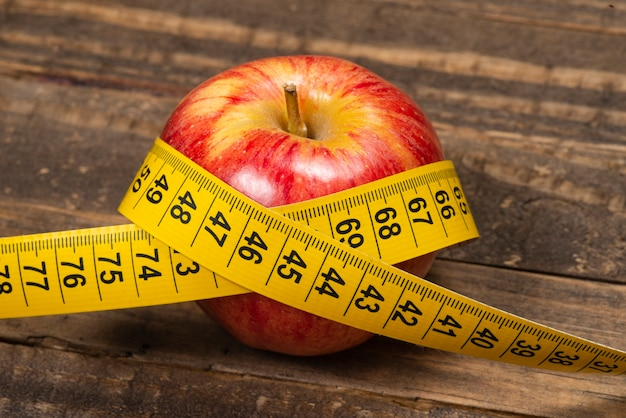 Apple with measuring tape, symbolizing overweight