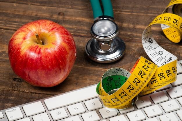 Яблоко с рулеткой, символизирующей лишний вес