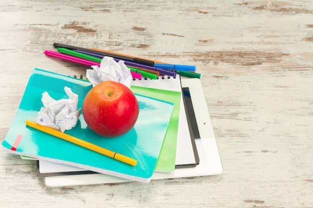 Apple with school supplies on aged white wooden table