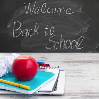 Яблоко со школьными принадлежностями на белом старом деревянном столе, доске и добро пожаловать обратно в школу