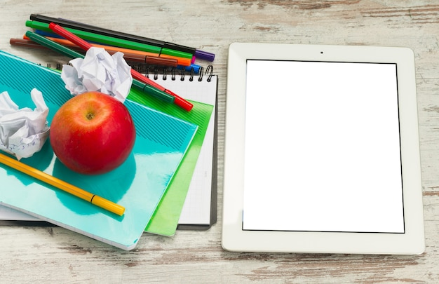 Apple with school supplies and tablet with empty screen on white wooden table