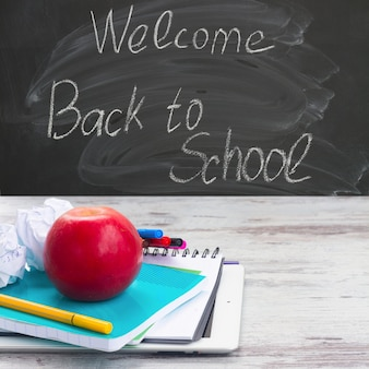 Apple with school supplies on white aged wooden table, blackboard and welcome back to school