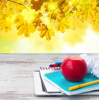 Apple with school supplies on white aged wooden table with fall leaves