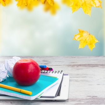 Apple with school supplies on white aged wooden table