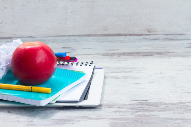 Apple with school supplies on white wooden table
