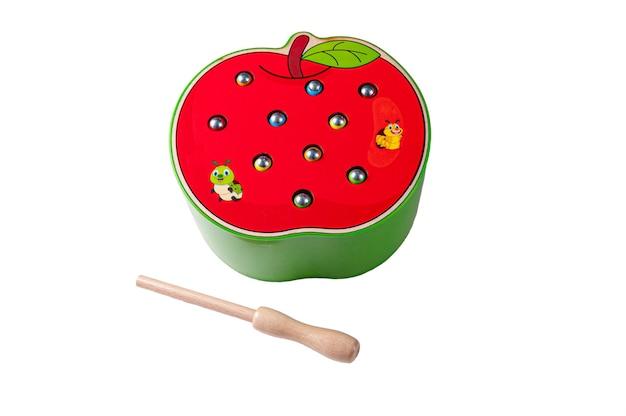 木で作られたワームを持つリンゴ。磁石の釣り竿でワームを捕まえます。教育玩具モンテッソーリ。白色の背景。閉じる。