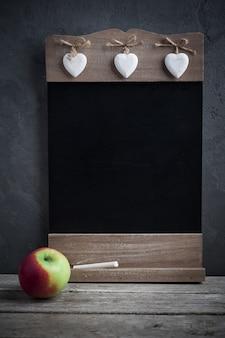 Apple and wooden blackboard