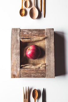 Apple in wooden old box with cutlery. sustainable lifestyle concept.