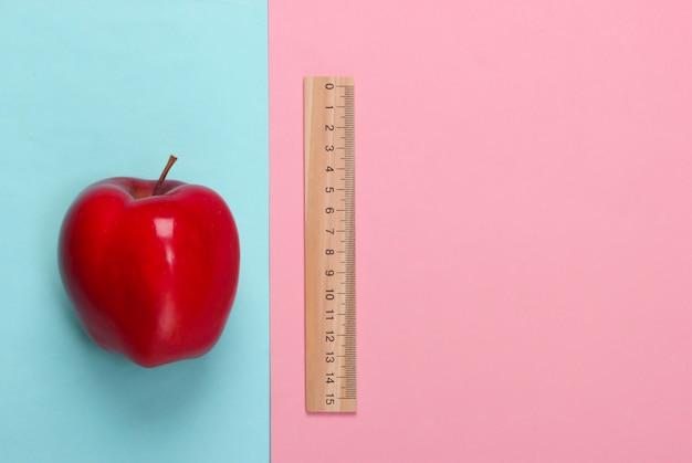 Яблоко, деревянная линейка на розовом синем. обратно в школу. концепция образования