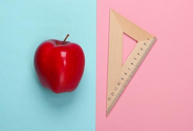 Яблоко, деревянный треугольник линейки на розовом синем. обратно в школу. концепция образования