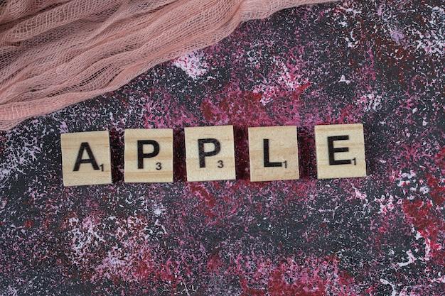 Scrittura di apple con la lettera taglia sulla superficie