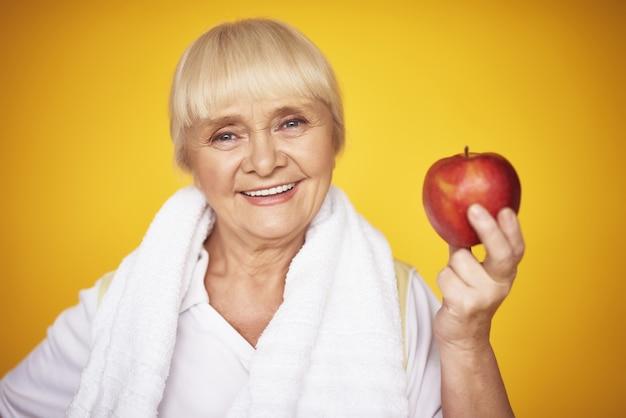 Женщина, держащая apple пожилая фитнес женщина диета.
