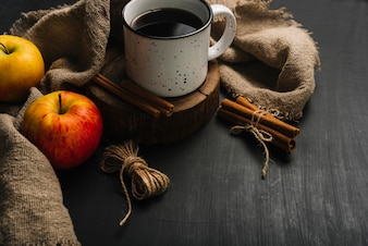 Apples and cinnamon near beverage and cloth